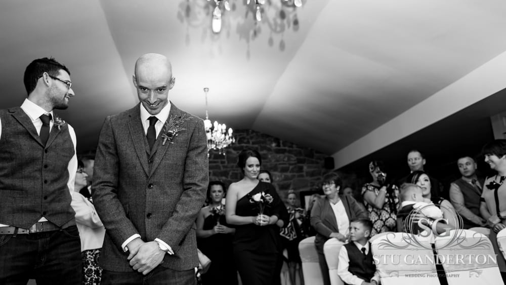 A groom waiting for his bride at the end of the aisle has a cheeky grin as he catches the eye of an approaching bridesmaid who is giving a suggestive look.