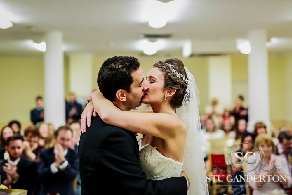 A bride and groom share a passionate embrace at when being told
