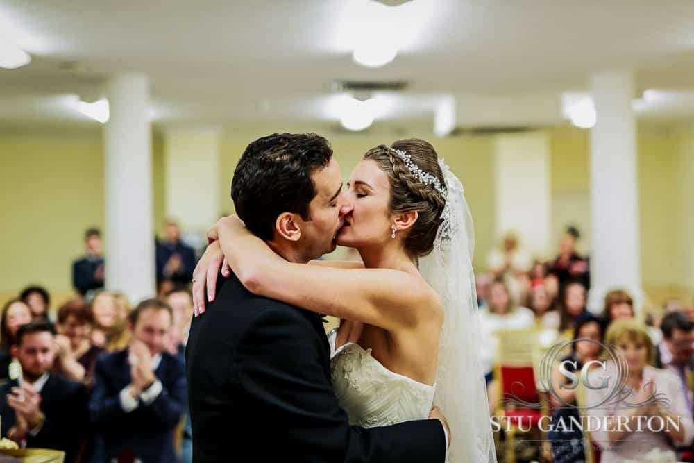 "A bride and groom share a passionate embrace at when being told ""you may now kiss your bride"" at the britannia hotel, portland street, manchester. Wedding photography, britannia hotel manchester. canon 5d mk3, sigma 50 1.4 art."