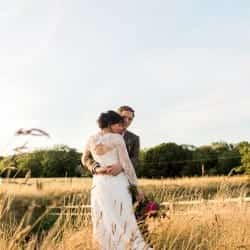 Bride and groom standing in long grass at tower hill barns llangollen