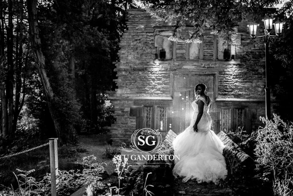 bride stands on the bridge in front of the folly at Bagden Hall Hotel, dramatically lit