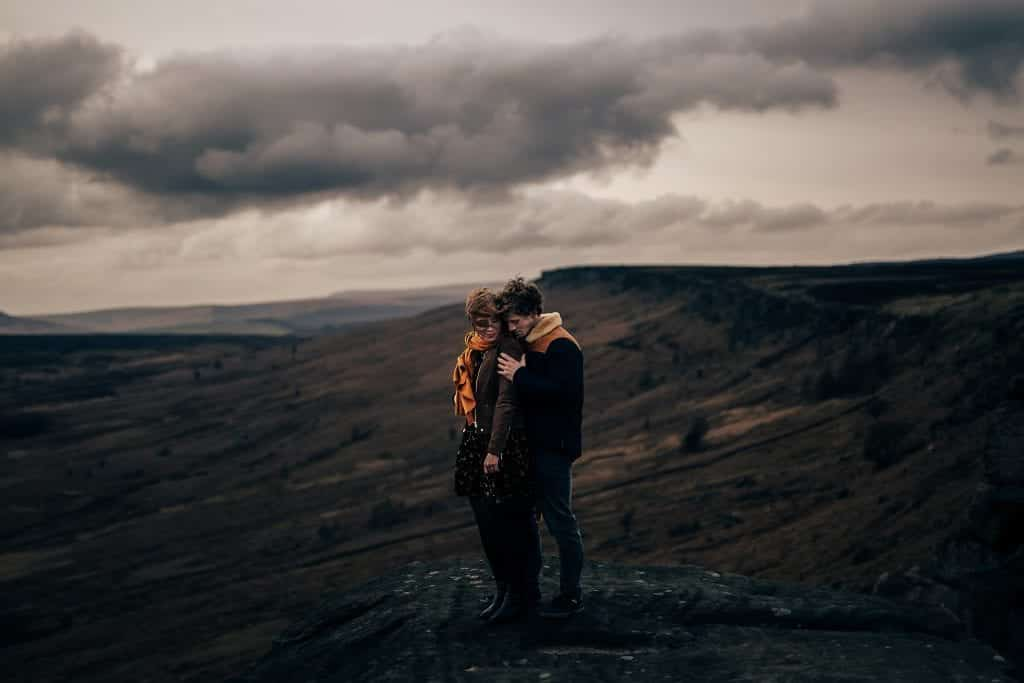 couple stand on hill, he is holding her from behind, she is wearing an orange scalf