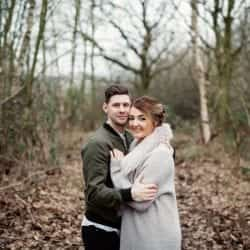 the happy couple stand holding each other in a forest looking at camera