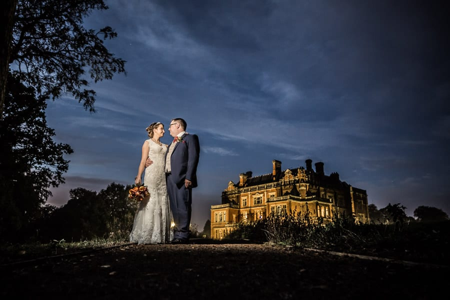 a night portrait of the bride and groom with the hall in the background at Rossington Hall Photography by Stu Ganderton Wedding Photography.