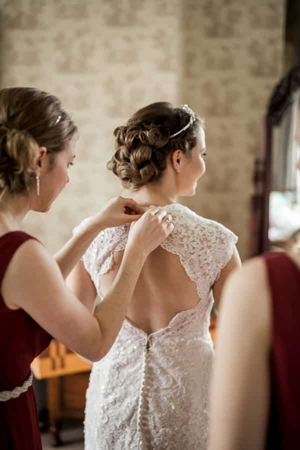 bridesmaids fasten up the dress at Rossington Hall Photography by Stu Ganderton Wedding Photography.