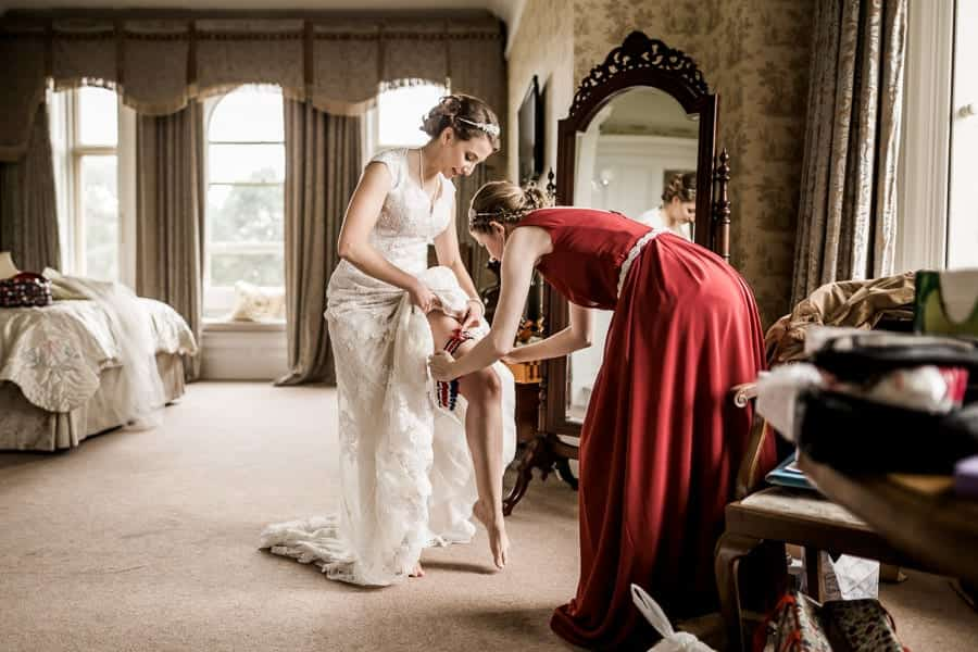 A bride puts on her garter helped by a bridesmaid at Rossington Hall Photography by Stu Ganderton Wedding Photography.