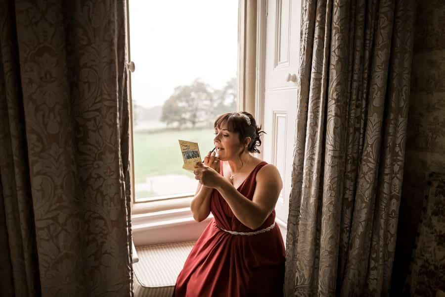 bridesmaid putting on her lipstick at Rossington Hall Photography by Stu Ganderton Wedding Photography.