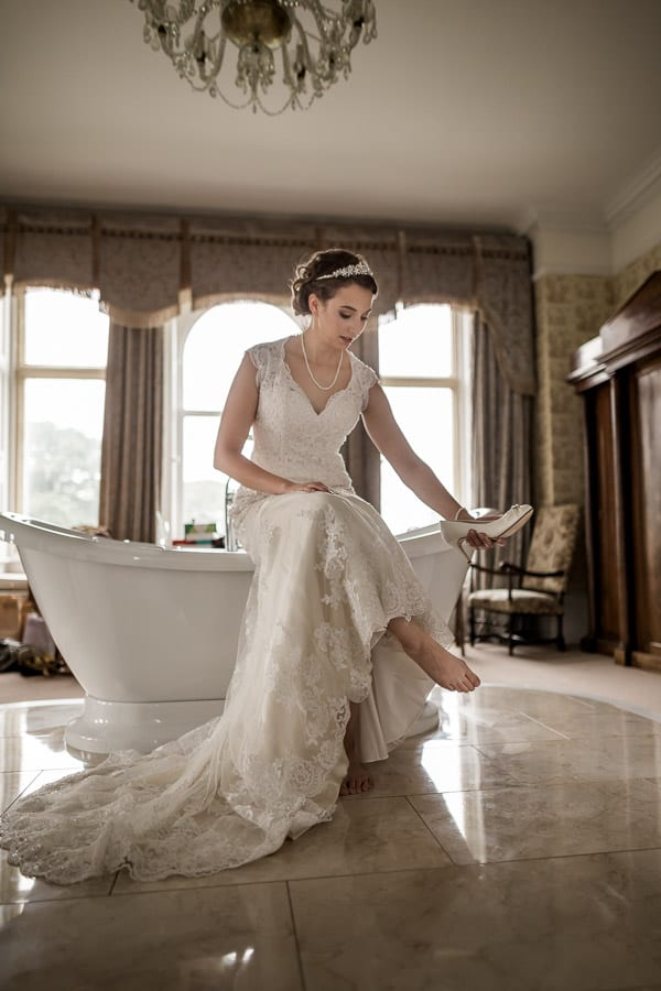 the bride putting on her shoe at Rossington Hall Photography by Stu Ganderton Wedding Photography.