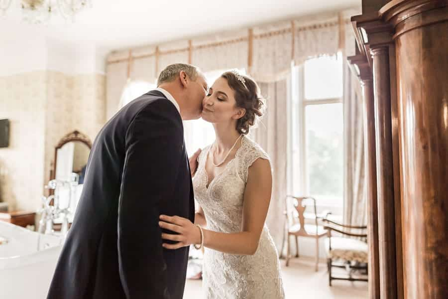 The father of the bride kisses her on the cheek at Rossington Hall Photography by Stu Ganderton Wedding Photography.