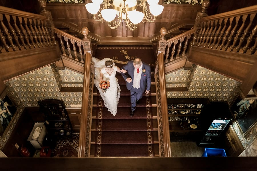 A father walks his daughter down the stairs to her wedding at Rossington Hall Photography by Stu Ganderton Wedding Photography.