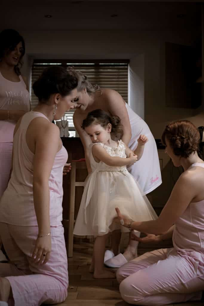 flower girl having her dress put on