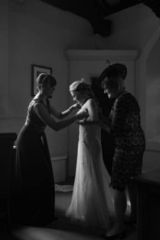 the bride has her dress done up by her mum and maid of honour at peckforton castle